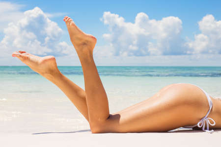 Photo pour Beautifully tanned legs on the beach - image libre de droit