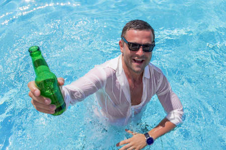 Young happy man partying in swimming pool