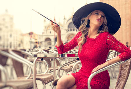 Fashionable woman smoking cigarette in style