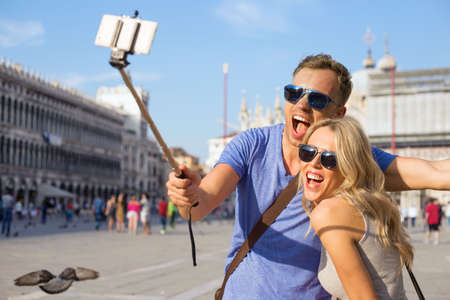 Funny tourist couple making selfie with selfie stick