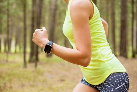 Photo pour Woman running with smartwatch - image libre de droit