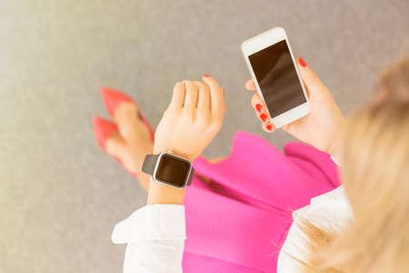 Photo pour Woman using smartwatch and cellphone - image libre de droit