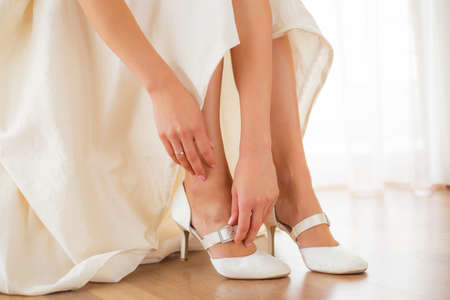 Photo pour Bride putting on her white shoes - image libre de droit