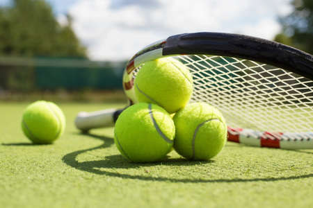 Foto per Tennis balls and racket on the grass court - Immagine Royalty Free