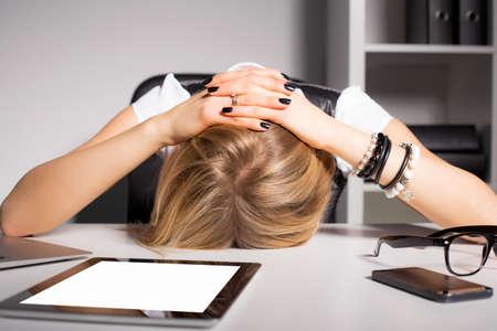 Foto de Tired business woman resting her head on desk - Imagen libre de derechos