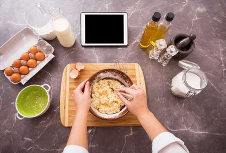 Photo for Woman preparing dough from recipe on her tablet - Royalty Free Image