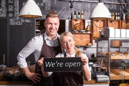 Photo pour Coffee shop owners showing open sign - image libre de droit