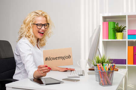 Photo for Woman in office showing I love my job cardboard - Royalty Free Image