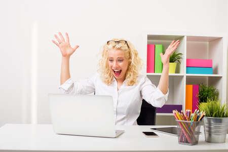 Photo pour Surprised and happy woman at the office showing her excitement - image libre de droit