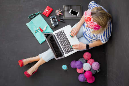 Photo for Modern woman sitting on the floor with computer in her lap - Royalty Free Image
