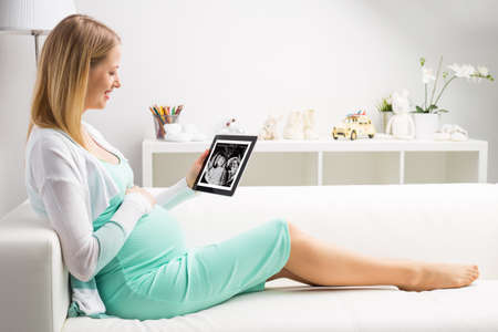 Photo for Pregnant woman looking at her babies first sonography results on tablet - Royalty Free Image