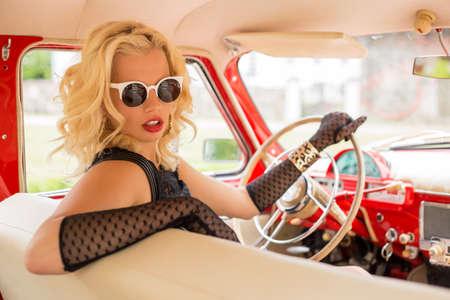 Foto de Sexy woman with sunglasses driving a retro car - Imagen libre de derechos