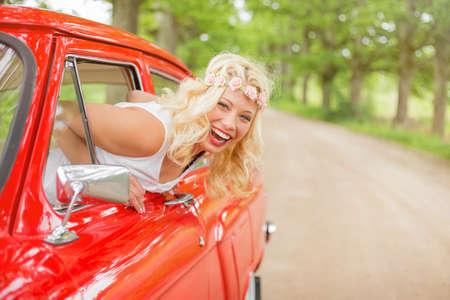 Photo pour Happy and cheerful woman hanging out of vintage car - image libre de droit