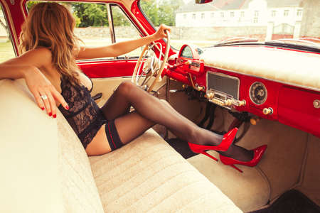 Sexy woman in underwear driving a vintage car