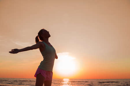 Happy and healthy woman standing in sunset
