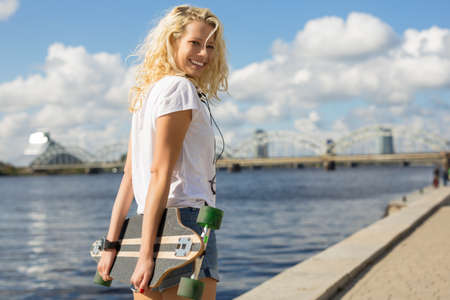 Woman in city environment holding longboard