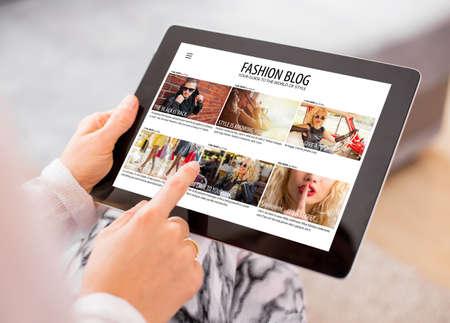 Foto de Woman reading fashion blog on tablet - Imagen libre de derechos