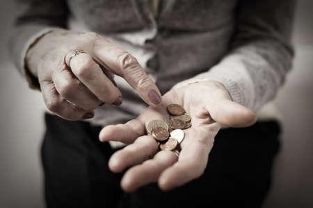 Photo pour Older person counting money in her palm - image libre de droit