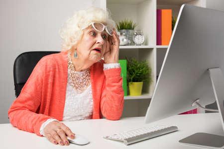 Foto de Grandma working at the office and looking at the computer in disbelief - Imagen libre de derechos