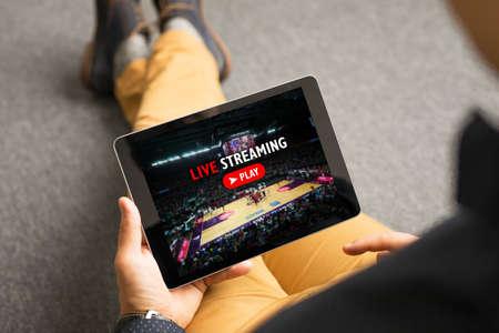 Photo pour Man watching sports on live streaming online service - image libre de droit