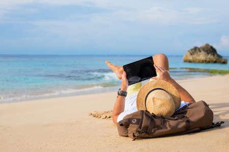 Foto de Man lying on the beach and using tablet - Imagen libre de derechos