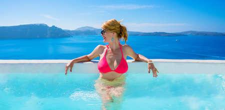 Foto de Woman in bikini relaxing in luxury outdoor pool - Imagen libre de derechos