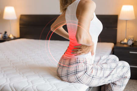 Photo pour Woman suffering from back pain because of uncomfortable mattress - image libre de droit