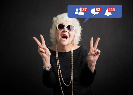 Photo pour Old woman still rocking and being active on social media - image libre de droit