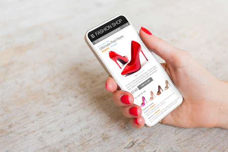 Photo pour Woman shopping online on her phone for new red high heels - image libre de droit