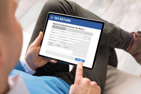 Photo pour Man submits electronic individual income tax return form - image libre de droit