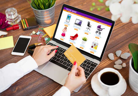 Photo for Woman shopping online on laptop and paying for purchased goods by credit card - Royalty Free Image