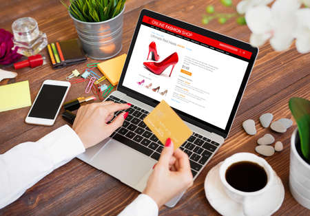 Photo for Woman buying new high heel shoes online and paying for purchase by credit card - Royalty Free Image