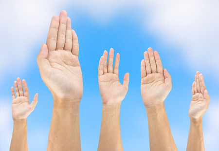 people raise hand on sky background