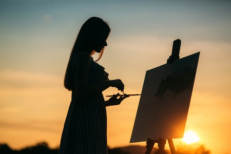 Silhouette of a blonde girl artist. Lady paints a painting on the canvas with the help of paints. A wooden easel keeps the picture. Summer is a sunny day, sunset