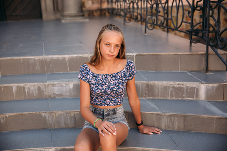 Photo pour teenage female dressed in jeans sits on stairs - image libre de droit