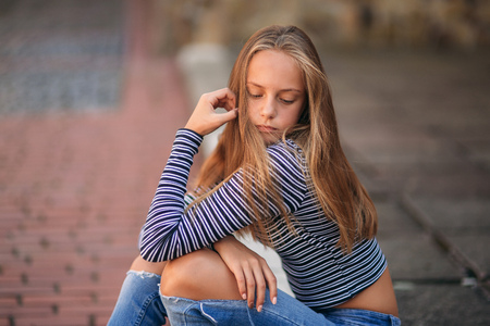 Photo pour young teenage poses to photographer. blonde girl in jeans and blouse - image libre de droit