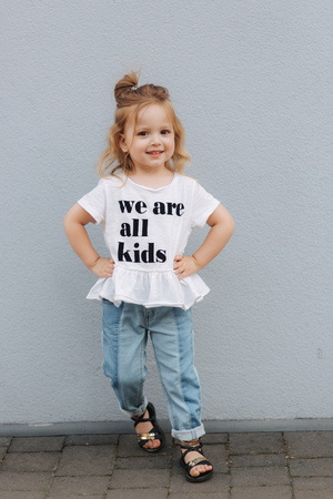 Photo for Beautiful little girl dressed in white shirt and jeans stand in front of gray wall. happy children - Royalty Free Image