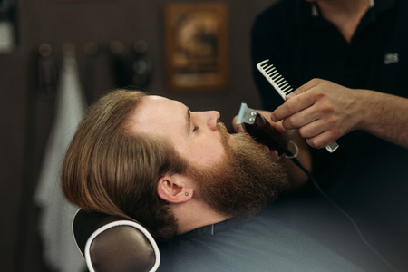 Foto per Bearded man having a haircut with a hair clippers - Immagine Royalty Free