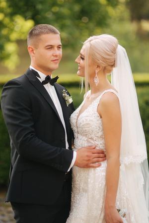Photo pour Handsome groom hug his beautiful bride. Newlyweds walking in the park. Blond hair woman in elegant wedding dress - image libre de droit