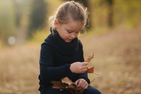 Photo pour A little girl in black clothes is sitting on a stump and playing with autumn leaves. Blond hair girl - image libre de droit