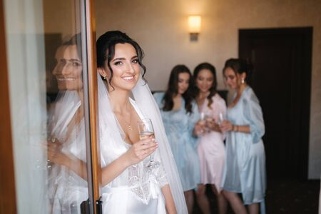 Foto de Gorgeous bride with best bridesmaids drinking champagne in hotel. Morning of bride. Sexy bridesmaids in exciting negligee - Imagen libre de derechos