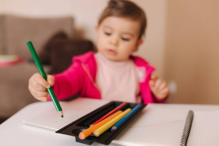 Photo pour Happy baby girl sit at the table and wthire something. Little girl use pencil for drawing on white paper at home - image libre de droit