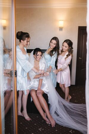 Foto de Gorgeous bride with best bridesmaids drinking champagne in hotel. Morning of bride. Sexy bridesmaids in exciting negligee - Imagen libre de derechos