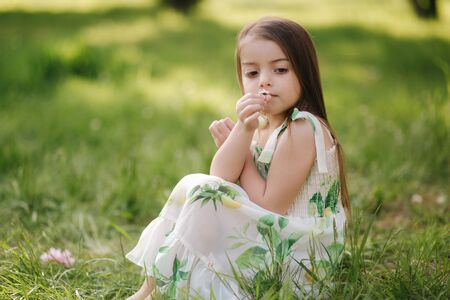 Photo pour Portrait of adorable little girl sits barefoot on the grass in the park. Happy kid on the fresh air - image libre de droit