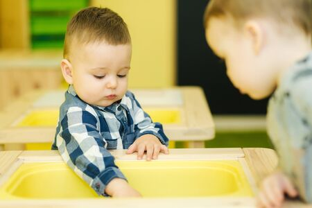 Photo pour Close up of children learning in preschool. Boy play with wooden toy - image libre de droit