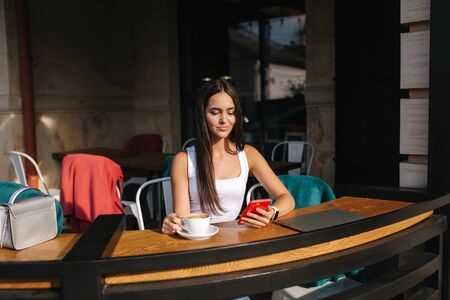 Photo pour Young business lady work on laptop and drinking a coffee. Beautiful girl sitting in cafe on terrace. Woman using phone and laptop outdoors - image libre de droit