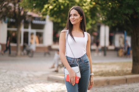 Photo pour Attractive young woman walking by herself in centre of city in summer time. Woman walk alone. Happy woman outdoors. Social distancing - image libre de droit