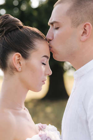 Foto für Close up portrait of groom kiss bride in forehead in front of big tree. Side view - Lizenzfreies Bild