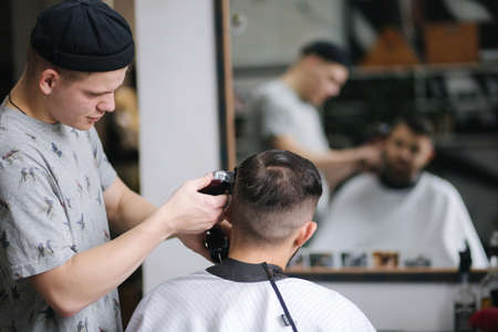 Photo pour Handsome man getting haircut by barber while sitting in chair at barbershop. - image libre de droit