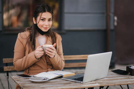 Photo pour Beautiful woman takes off protective mask for drinking coffee. Female sitting outdoors on terrace and drink coffee. Quarantine, self distancing - image libre de droit